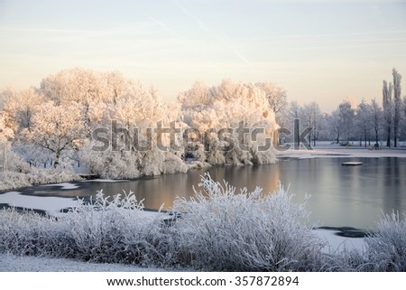 Small lake partly covered with ice and snow and bordered by trees glowing in the light of rising sun, Alblasserdam, South Holland, Netherlands