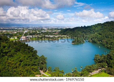 Small lake surrounded by trees with a city in the background. - stock photo