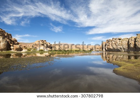 Small lake with green grass and strange geological formations against a cloudy blue clear sky in Bolivia. Landmark close to the border of Chile and the Salar of Uyuni. Bolivia - stock photo