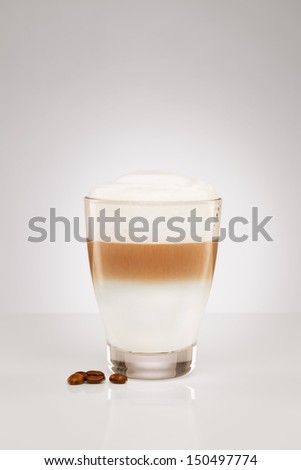 small latte macchiato in a glass cup with coffee beans on gray background - stock photo