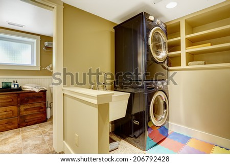 Small laundry area in bathroom. View of black modern appliances - stock photo