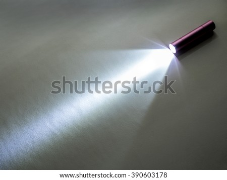 small LED flash light illuminated on the floor with white shine - stock photo