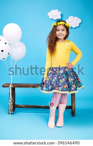 Small little beautiful pretty cute girl dark hair hat with flowers wear fashion style trend clothing dress skirt blouse shoe smile play with bench and balloons dance jump children kid happy daughter - stock photo