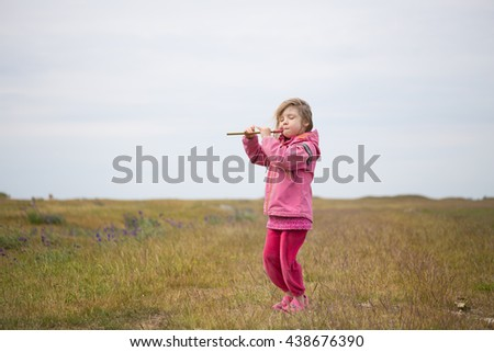 small little girl in preschool age standing on rural field and playing on fife at grey weather, in scandinavia - stock photo