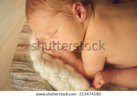 Small little newborn baby in basket - stock photo