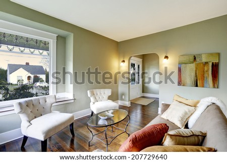 Small living area with two classic chairs, glass top coffee table and brown sofa with pillows and fur rug - stock photo