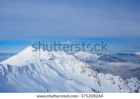 small lodge building on the top of mountains covered with snow in sochi Rosa Khutor ski resort and landscape view of the valley - stock photo