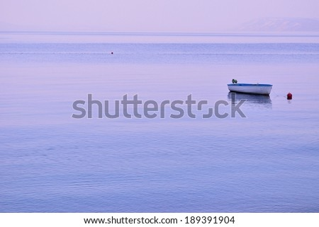 Small lonely fishing boat floating on flat surface of adriatic sea on calm morning  - stock photo