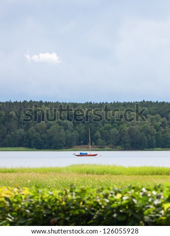 Small, lonely, sailboat anchored on a calm river beneath a moody sky.