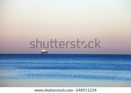 Small lonely ship floating on flat surface of sea on calm morning.  - stock photo
