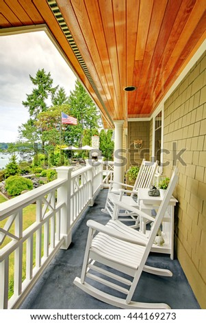 Small long balcony home exterior with white rocking chairs and water view.