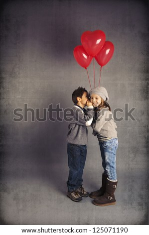 Small loving couple of kids with red heart balloons on vintage background. Valentines day concept.