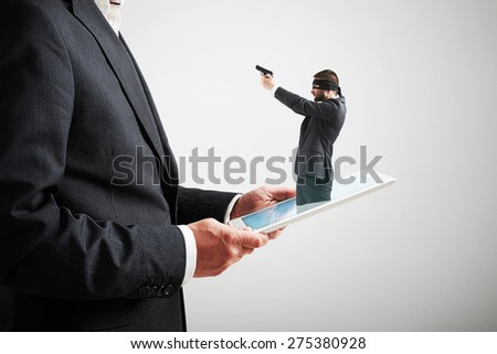 small man in mask and with gun got out of the tablet pc, and aiming at the big man over light grey background. cybercrime concept - stock photo