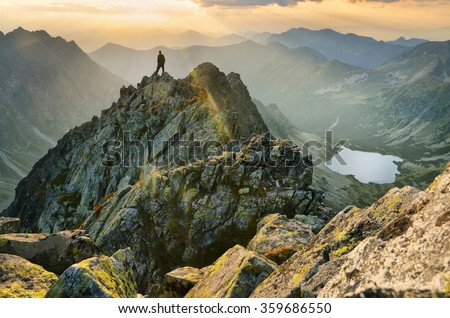 small man on the top of mountains in slovakia during calm summer sunset - stock photo