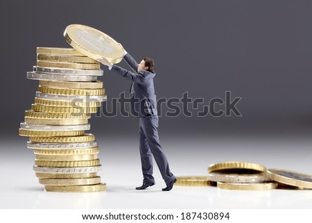 Small man stacking Euro coins. Money investment concept.  - stock photo