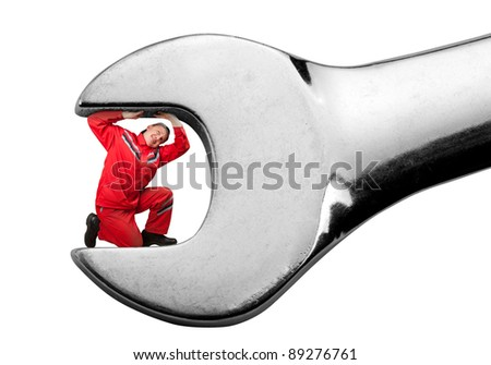 Small mechanic clamped inside big spanner. Isolated - stock photo