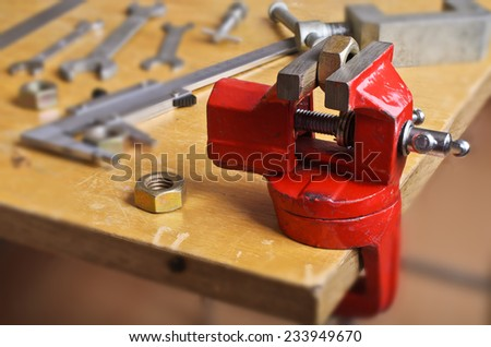 Small mechanical grip and pressed them in with a metal nut on the background of other instruments - stock photo