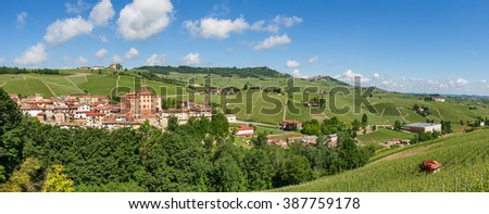 Small medieval town of Barolo, green hills and vineyards under blue sky in Piedmont, Northern Italy (panorama).