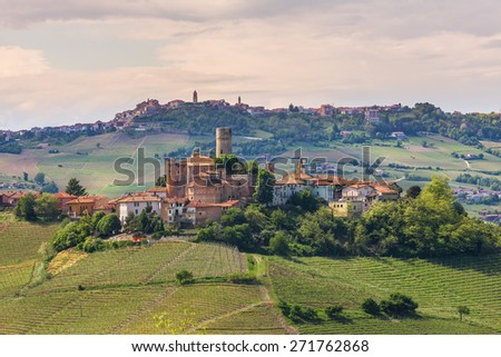 Small medieval town on the hill with vineyards in Piedmont, Northern Italy. - stock photo