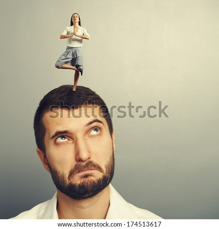 small meditation woman standing on the head of thoughtful man