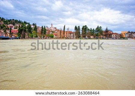Small Mediterranean town along the swollen river and threatening flood - stock photo