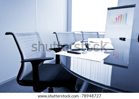 Small meeting room with flip chart, chairs and glass table. - stock photo