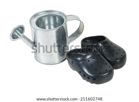 Small metal watering can and rubber gardening shoes - path included - stock photo