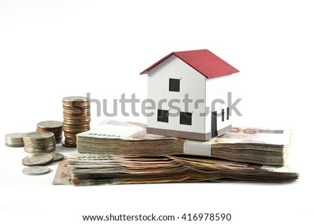 Small model house with stacks of Thai banknotes and coins on white background
