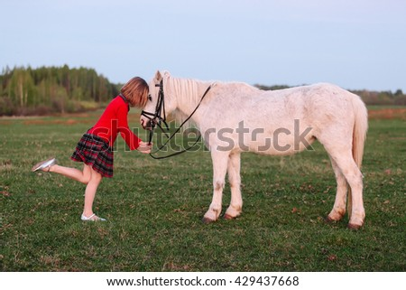 Small model of a young girl put her child in a small white pony Outdoors - stock photo
