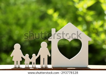 Small model of house and family on blurred background - stock photo
