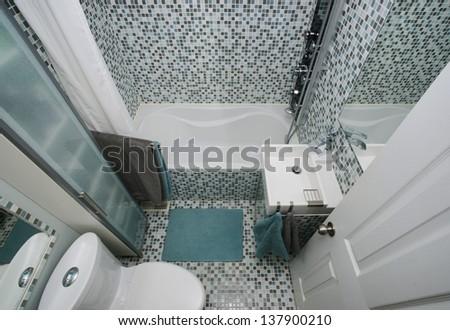 Small, modern bathroom interior. Mosaic tiles. White. Gray. Blue. Well organized space. - stock photo