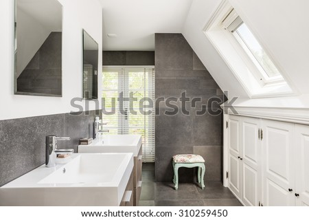 Small modern bathroom with double sink and dark tiles - stock photo