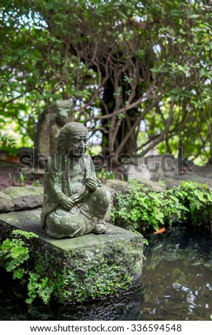 small monk statue in the garden - stock photo
