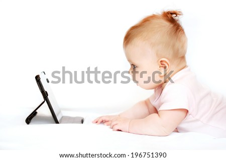 Small 3 months baby with a tablet pc at home on a white background - stock photo