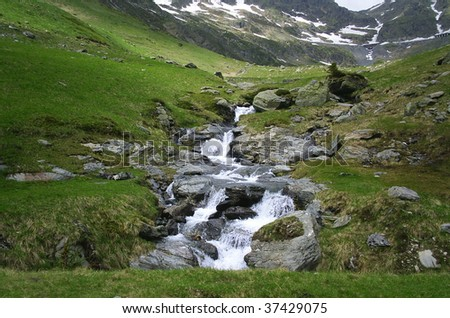 Small mountain creek with waterfall in the forest - stock photo