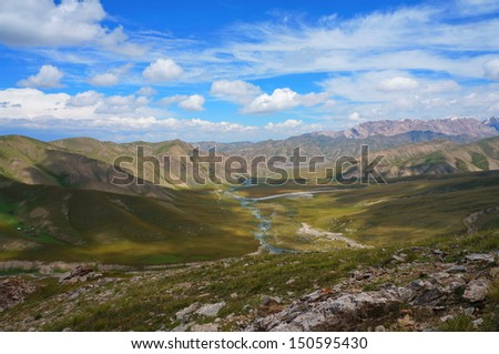 Small mountains, the river and amazing  blue sky with white clouds in Kyrgyzstan