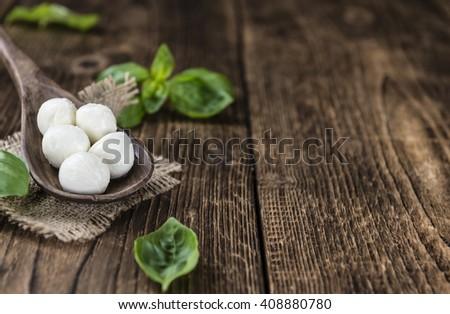 Small Mozzarella balls (on wooden background; selective focus) as close-up shot - stock photo
