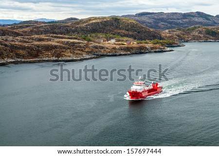 Small Norwegian red oil products tanker ship sails in fjord - stock photo