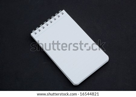 Small notepad isolated on a dark background - stock photo