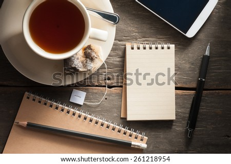 Small notepad with a cup of tea, pen, pencil and cellphne on rustic wood background with low key scene - stock photo