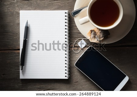 Small notepad with a cup of tea, pen, pencil and cellphne on rustic wood background with low key scene