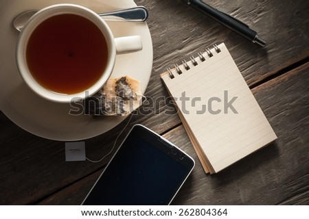 Small notepad with a cup of tea, pen, pencil and cellphone on rustic wood background with low key scene - stock photo