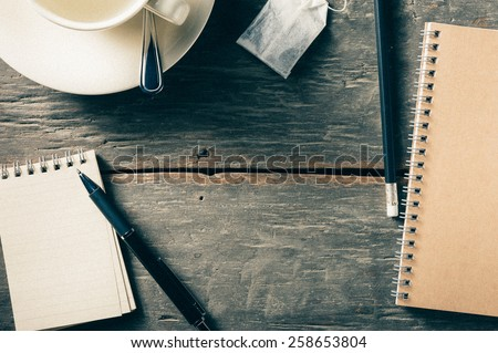 Small notepad with empty coffee cup, tea bag, pen and pencil on rustic wood background with film filter effect - stock photo