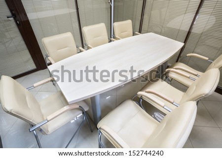 Small office blinds closed with a table and leather chairs - stock photo