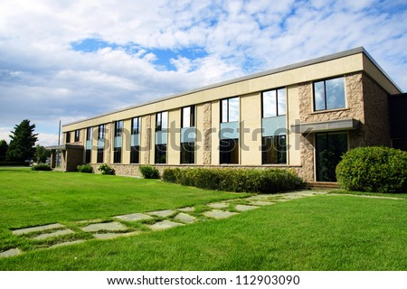 Small office or business building or college school perspective shot with sky and grass. - stock photo