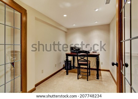 Small office room interior in soft ivory with wooden desk and chair - stock photo