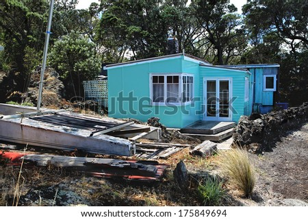 Small old beach house with boat alongside - stock photo