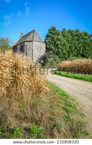Small old medieval building in dry ripe corn field with curved road, France, Brittany - stock photo