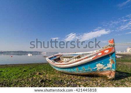 Small, old traditional boat in Seixal bay. Portugal. - stock photo