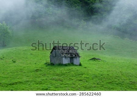 Small old wooden house in foggy forest. Mountains scenery. Nature conceptual image. - stock photo